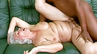 Short haired granny Norma with natural hanging tits and pale skin gets her hairy cunt boned deep to long forgotten orgasm by turned on young black buck on leather couch